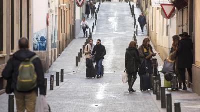 Turistas con maletas por una de las calles del céntrico barrio madrileño de Huertas. / Fernando Sánchez