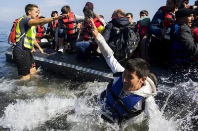 Varias personas saltan de una lancha neumática al llegar a una playa próxima a Skala Sikaminias tras atravesar el Mar Mediterráneo procedentes de Turquía, en la isla de Lesbos (Grecia), a principios de octubre. / EFE