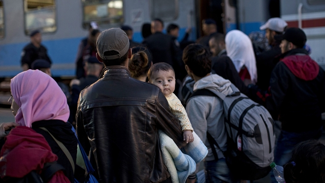 People queue in order to board a train close to Croatia's border with Serbia, in Tovarnik, Croatia, Tuesday, Sept. 22, 2015. European Union ministers agreed Tuesday to relocate 120,000 migrants in a move intended to ease the strain on nations Greece and Italy which are on the frontline of the continent's overwhelming migrant crisis. (AP Photo/Marko Drobnjakovic)