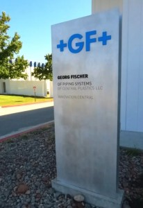 Picture of metal monolith type sign in front of building, silver with blue letters.