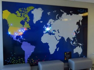 Photo of a large map of the world with different colored LED pin lights in various areas.