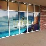 An angled view of 5 store front windows with vinyl graphics.