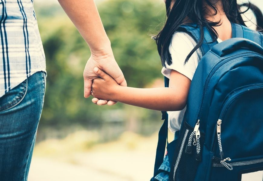 school girl holding hands with mother