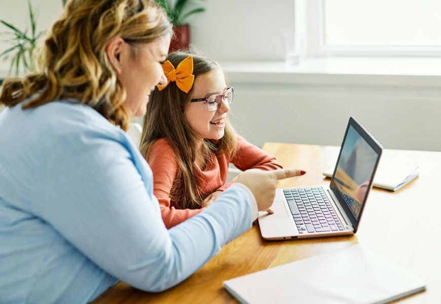 parent helping girl on laptop