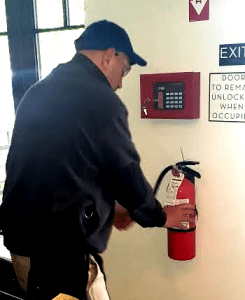 ESC Tech inspects a fire extinguisher per fire code (image)
