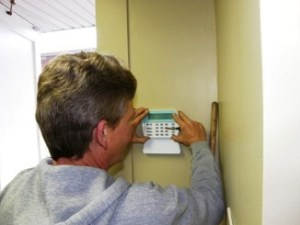 An ESC Technician installs a keypad in a commercial business (image)