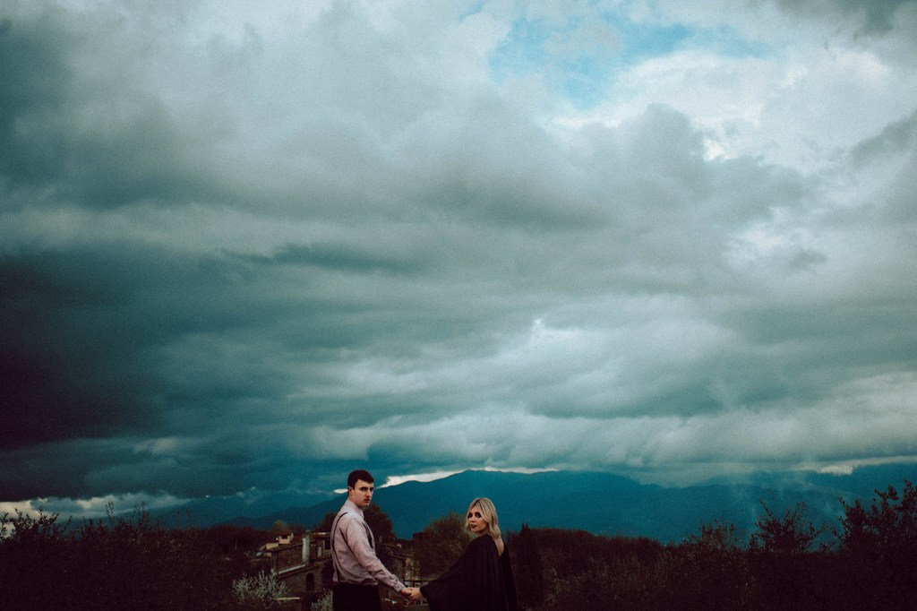 Tuscany Engagement Session - Couple walking with Tuscany countryside and moody sky in the background