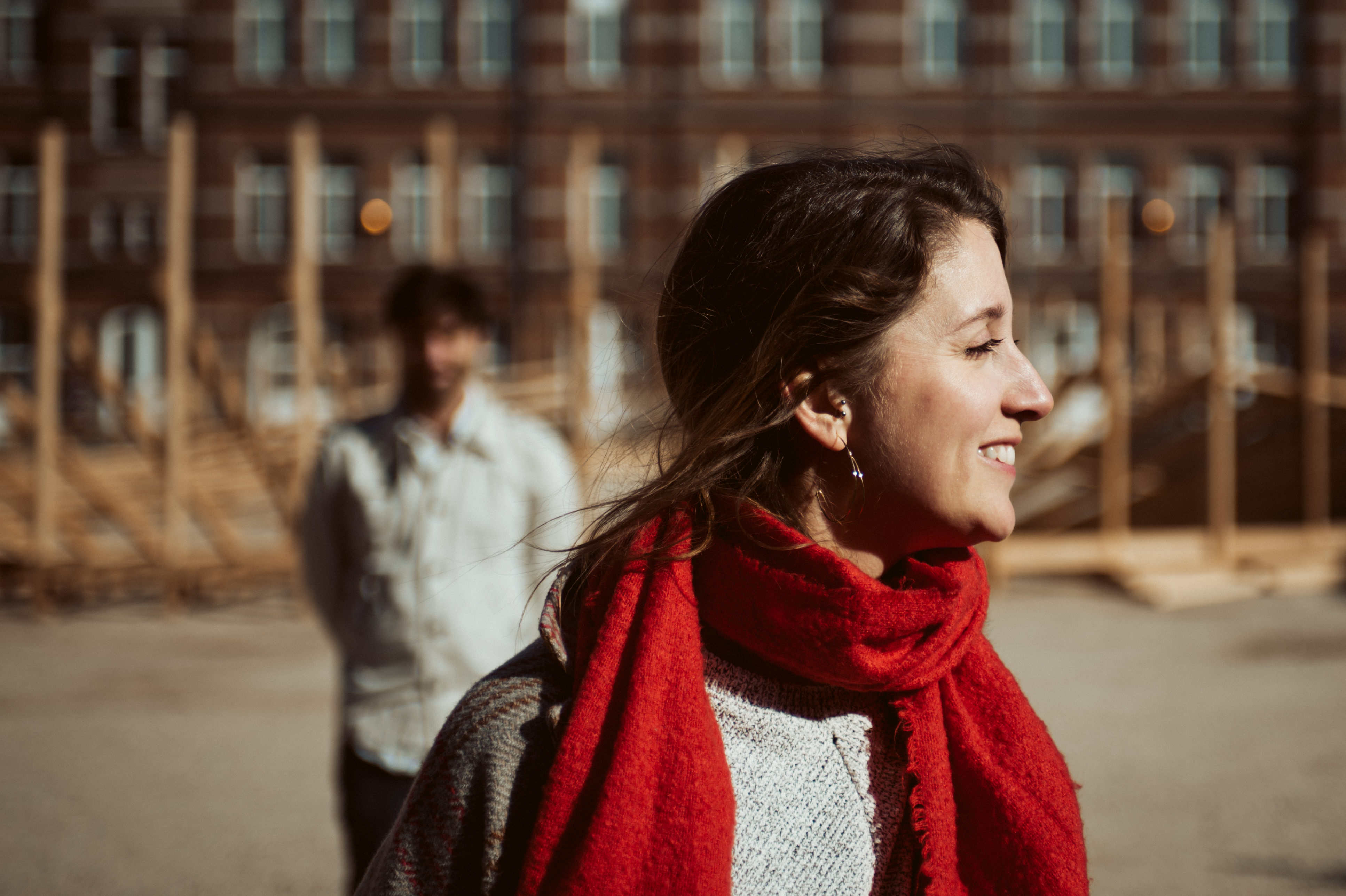 Brussels Engagement Session - girlfriend staring at the sun, he's int he background
