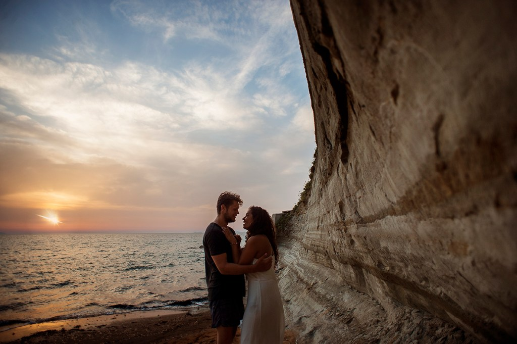 Greece Destination Engagement - Corfu - couple hugging next to a big rock, with sunset in background