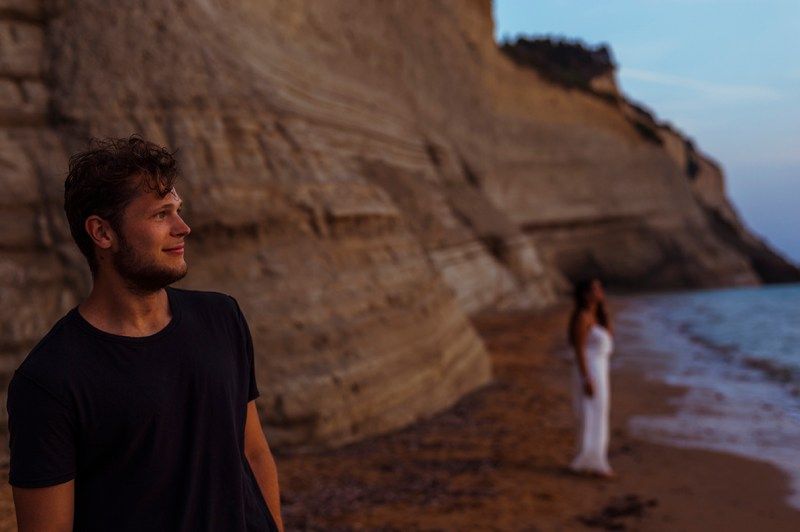 Greece Destination Engagement - Corfu - Boyfriend staring at the sunset, girlfriend in the background