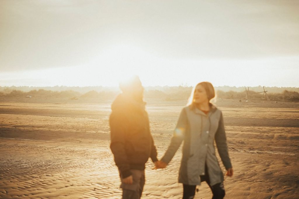 couple walking on a beach, blurred subjects