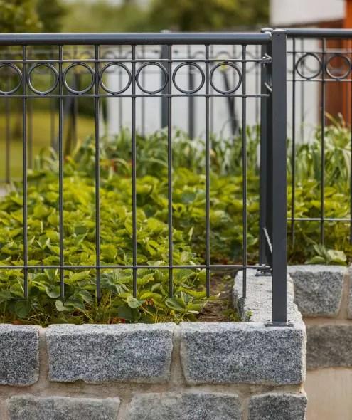 Gartengeländer auf Steinmauer und begrünt