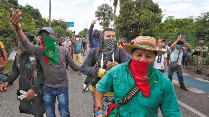 AME6417. CALI (COLOMBIA), 09/05/2021.- IndÌgenas caminan por una calle durante una manifestaciÛn hoy en Cali (Colombia). Varias autoridades denunciaron que este domingo supuestos civiles armados dispararon contra un grupo de indÌgenas que estaban manifest·ndose a las afueras de la ciudad colombiana de Cali, dejando varios heridos. EFE/ Pablo RodrÌguez