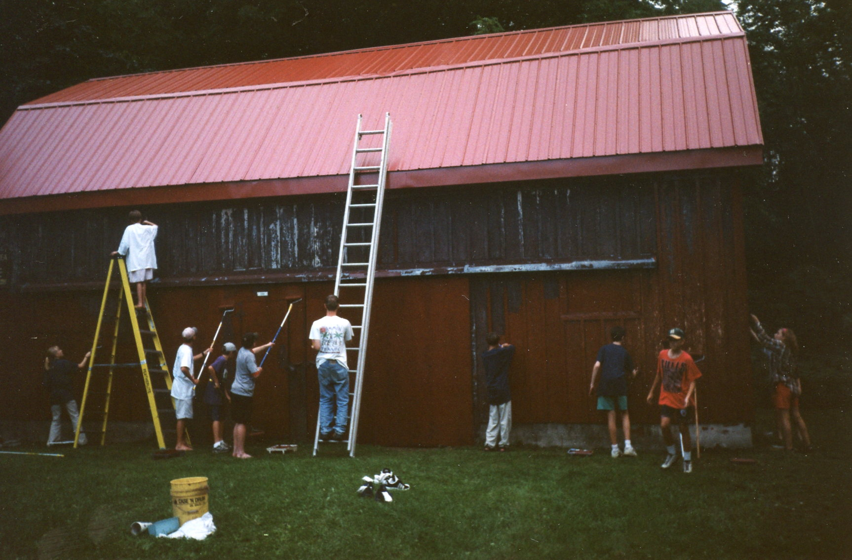 Volunteers hard at work putting fresh coat of paint on red barn in 2000.