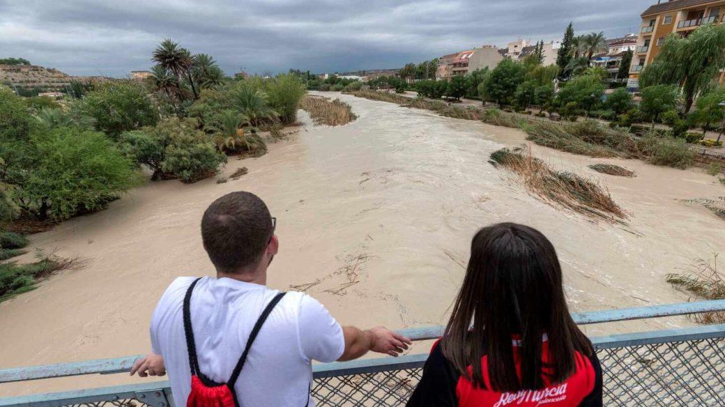 Dos chicos observan la crecida del río Segura tras desbordarse por los dos márgenes a su paso por Archena, Murcia
