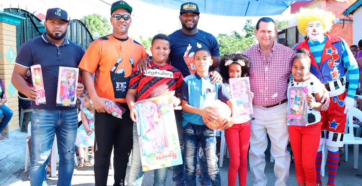 El pelotero de grandes ligas Hanser Alberto junto al senador Amilcar Romero y el pelotero de grandes ligas Kelvin Gutiérrez entregan juguetes a decenas de niños de la comunidad de Guiza.