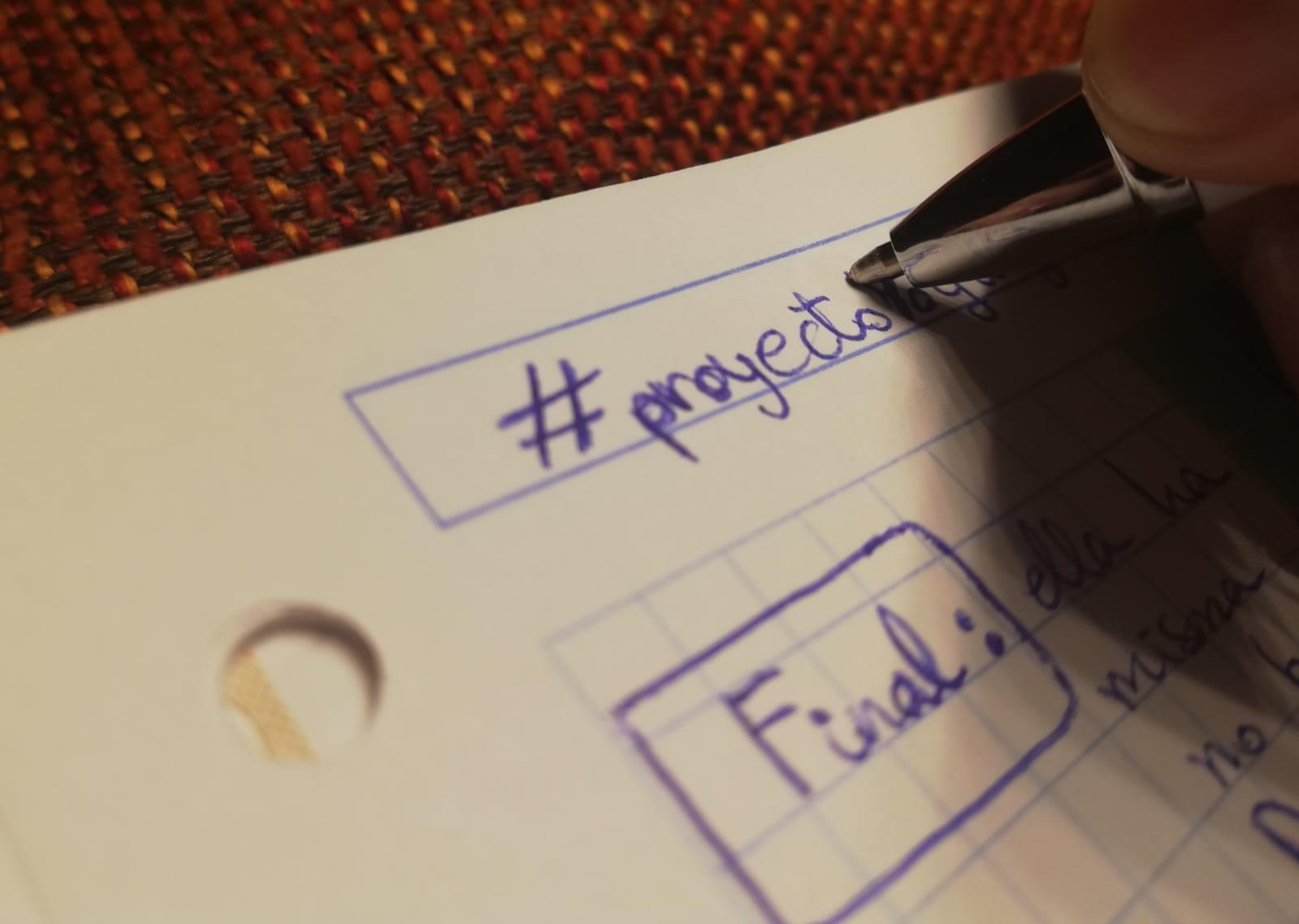 """Mano escribiendo en una libreta donde pone """"#proyecto"""""""
