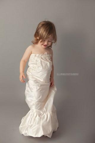 Child wearing mommy's wedding dress
