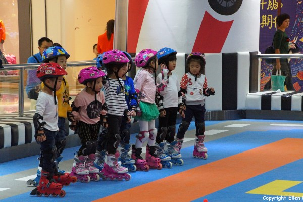 Kids learning roller skating in a big warehouse at Chengdu