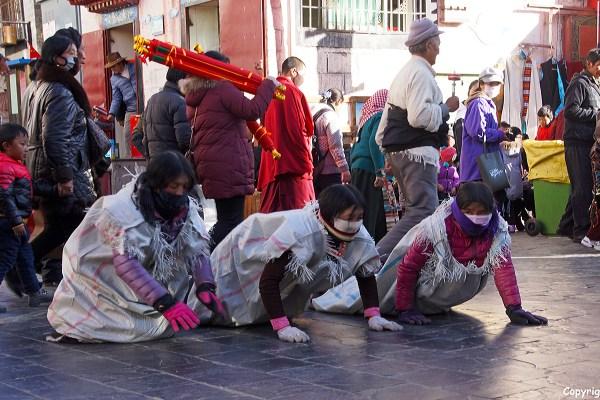 Lhasa, Barkhor Street. Pilgrims prostrating around the holy Jokhang Temple.