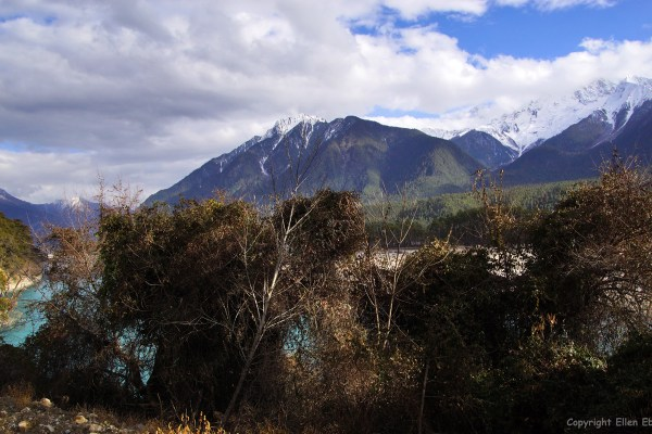Driving through a beautiful river valley with white mountain tops and glaciers in eastern Tibet.