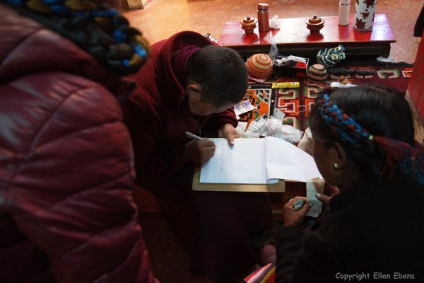 Nun writing down wishes of pilgrims at Rabse Nunnery, Gyantse