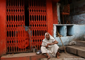 Old woman resting in front of a sanctuary in the city of Omkareswar