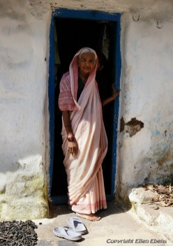 Old woman in the doorway of her house in the city of Bijapur