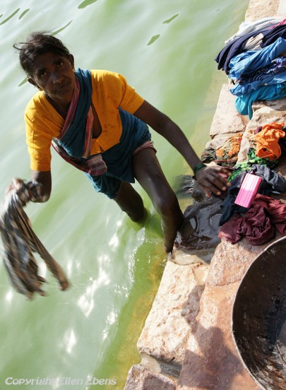 Woman washing clothes at the ghats at the small town of Badami
