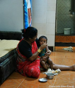 Mother feeding her little child in the big city of Mumbai