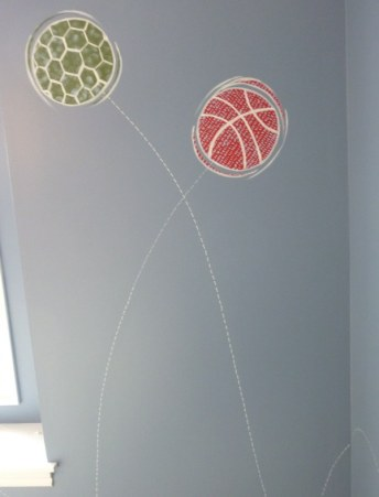 Stylized graphics of bouncing balls to coordinate with boy's bedding. Mural by Ellen Leigh