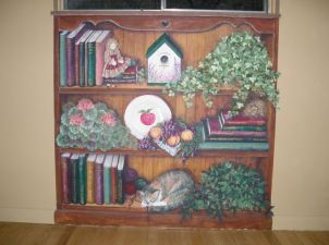 Book case mural on a wall below a window to look built in. Filled with favorite book titles and favorite pastimes of the family. Portrait of a favorite cat. Mural by Ellen Leigh