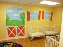 Cartoonish windows and farm scene in baby nursery in the day care. Mural by Ellen Leigh