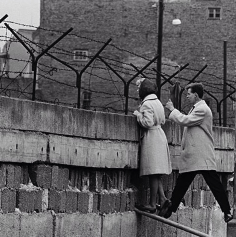 A young West Berlin couple peer over the Wall as the woman speaks to her mother in East Berlin, 1960s.