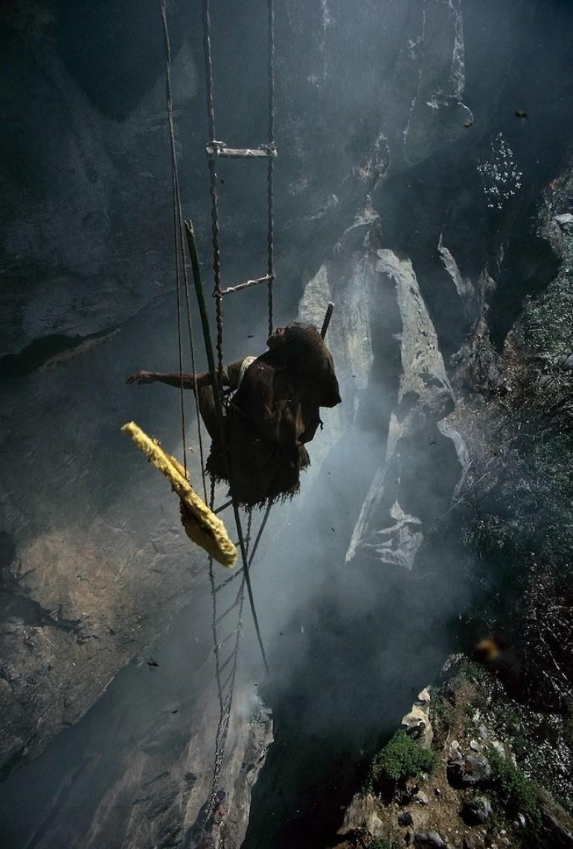 man hanging off mountain