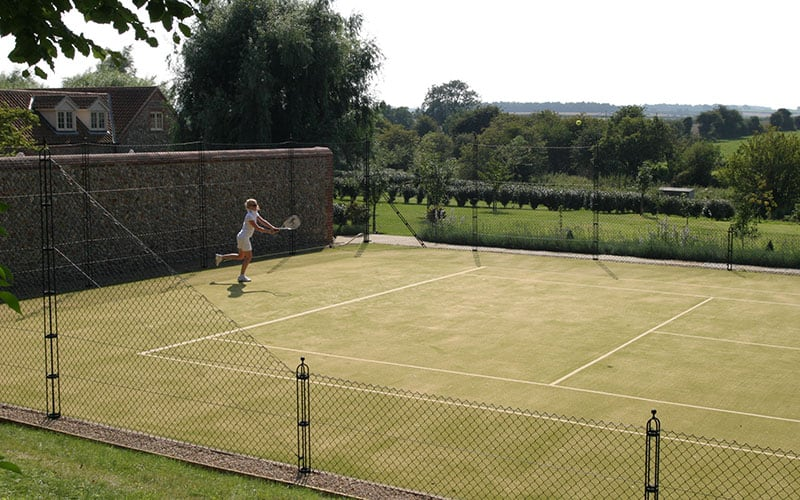 An old flint wall forms a beautiful backdrop to this tennis court by En Tout Cas