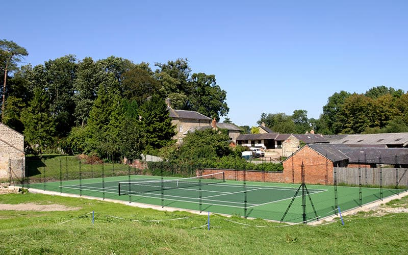 Rural setting for a tennis court by EnTC - tennis court construction specialists.