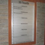 Interior brushed aluminum directory sign with frosted acrylic slats, vinyl graphics and brushed aluminum standoffs
