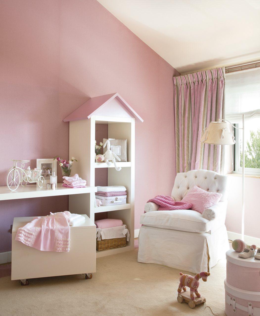 Zona con butaca y almacenaje. Dormitorio infantil blanco y rosa con sillón y estanterías