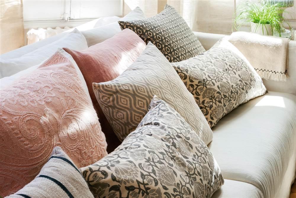 Cojines en rosa, gris y verde con estampados florales y bordados sobre sofá blanco