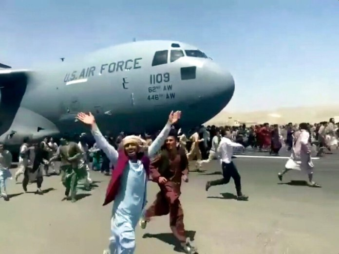 Hundreds of people run alongside a U.S. Air Force C-17 transport plane as it moves down a runway at the international airport in Kabul, Afghanistan, on Aug. 16, 2021.