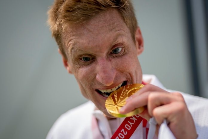 Brad Snyder rips off the gold medal he won in the triathlon of the Paralympic Games in Tokyo.