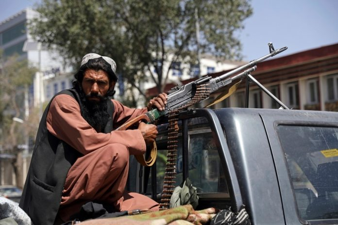 A member of the Taliban sits in the back of a machine-gunned vehicle in front of the main gate leading to the Afghan presidential palace in Kabul, Afghanistan.