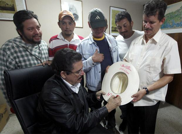 Zelaya firmando un autógrafo en un sombrero