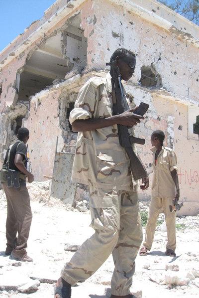 Soldado mercenario de Somalia entre escombros.