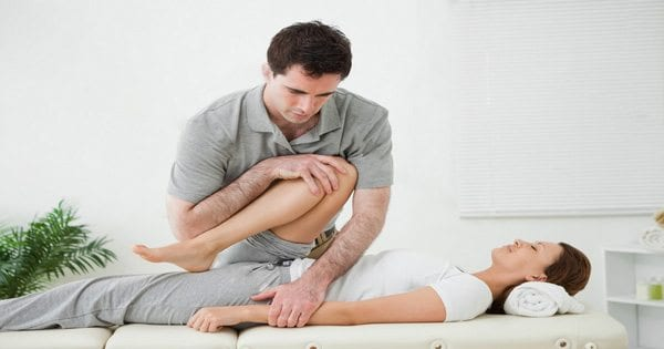 blog picture of a lady having her leg stretched by a chiropractor