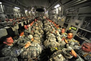blog picture of soldiers on a plane with all their equipment in their laps