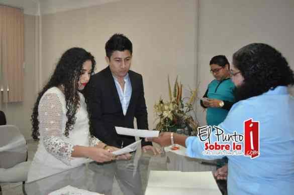 .- La juez Damiana Rivera Gil entrega el acta de matrimonio a los recién casados.