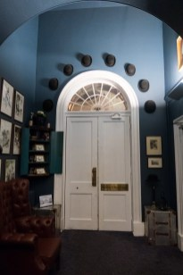 7 bowler hats above the door leading to the restaurant from inside to represent those hanged