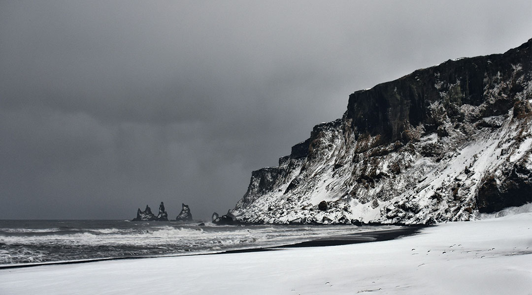 Jsland Reynisdrangar aan het zwarte strand in Vík